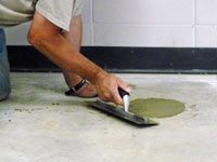 Repairing the cored holes in the concrete slab floor with fresh concrete and cleaning up the Burlington home.