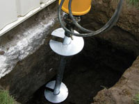 Installing a helical pier system in the earth around a foundation in Hamilton