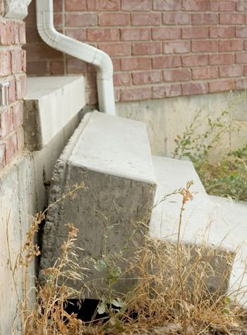 sinking outdoor concrete steps showing cracking and soil washout in Newmarket